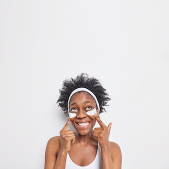 Vertikale aufnahme einer glücklichen, lockigen afro-amerikanerin zeigt auf die augenklappen und lächelt breit
