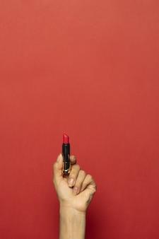 Vertikale aufnahme einer hand, die einen lippenstift isoliert auf einer roten wand hält