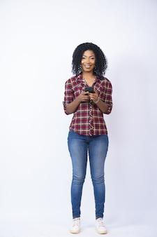 Vertikale aufnahme einer hübschen schwarzen frau, die lächelt, während sie ihr telefon benutzt
