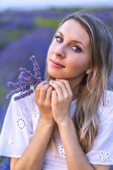 Vertikale aufnahme einer jungen dame, die in einem lavendelfeld posiert