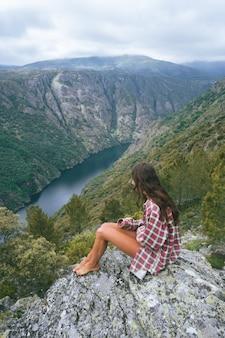 Vertikale aufnahme einer jungen kaukasischen frau im sil canyon in spanien