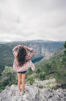 Vertikale aufnahme einer jungen kaukasischen frau in sil canyon in spanien