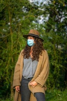 Vertikale aufnahme einer jungen kaukasischen frau mit einer medizinischen maske