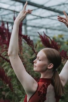 Vertikale aufnahme einer kaukasischen balletttänzerin, die im burgunderfarbenen kostüm aufwirft