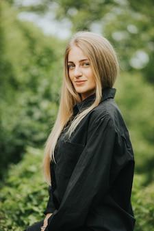 Vertikale aufnahme einer modischen kaukasischen blonden frau, die durch grün umgeben aufwirft