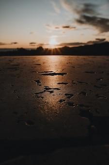 Vertikale aufnahme einer nassen oberfläche, die das sonnenlicht reflektiert