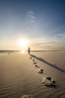 Vertikale aufnahme einer person, die am sandstrand mit schritten im vordergrund spaziert
