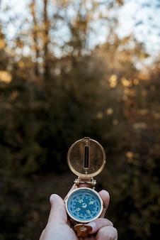 Vertikale aufnahme einer person, die einen kompass mit einem unscharfen natürlichen hintergrund hält
