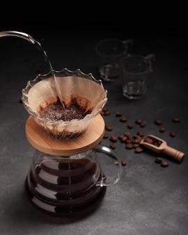 Vertikale aufnahme einer person, die kaffee in glas auf schwarzem hintergrund gießt