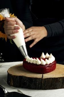 Vertikale aufnahme einer person, die weiße sahne auf einem schicken roten samtkuchen in herzform hinzufügt