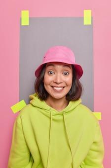 Vertikale aufnahme einer schönen asiatischen frau mit dunklem haar, die zahnig lächelt, trägt rosa panama und grünes sweatshirt sieht froh aus, posiert hinter einem verputzten blatt papier