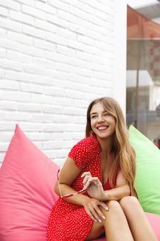 Vertikale aufnahme einer schönen frau, die spaß in einem straßencafé hat, sitzend auf sitzsackstuhl