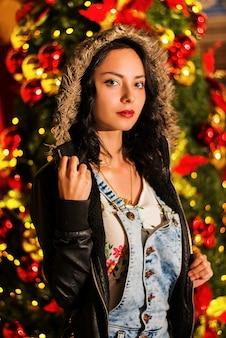 Vertikale aufnahme einer schönen jungen dame vor einem weihnachtsbaum