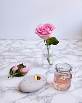 Vertikale aufnahme einer schönen rosa rose und blumenobjekte auf einer oberfläche