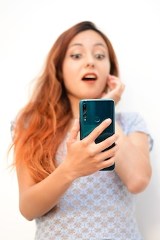Vertikale aufnahme einer schönen rothaarigen dame, die ihr telefon anschaut, schüttelte