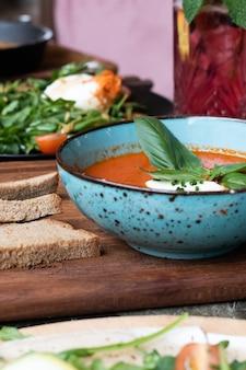 Vertikale aufnahme einer schüssel tomatensuppe und eines tellers salat und brot auf einem holzbrett