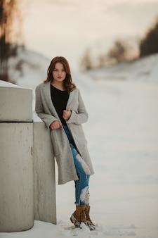 Vertikale aufnahme einer sexy frau mit einer grauen jacke, die sich in einem verschneiten park an die wand lehnt