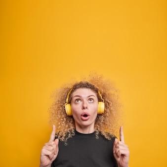 Vertikale aufnahme einer überraschten, verwunderten jungen frau mit lockigen haarspitzen oben zeigt erstaunliche werbung, die musik über kopfhörer hört, trägt ein lässiges gelbes t-shirt isoliert über gelber wand?