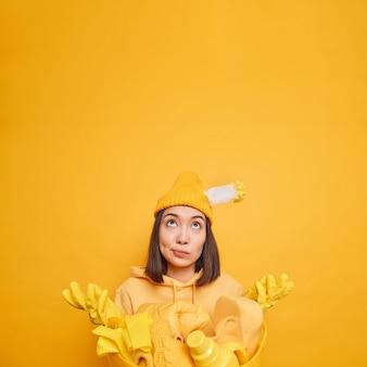 Vertikale aufnahme einer verwirrten asiatischen frau breitet die nach oben gerichteten handflächen mit unentschlossenem ausdruck aus, weiß nicht, wovon sie mit der reinigung beginnen soll, trägt gummihandschuhe, wäscht zu hause isoliert auf gelber wand