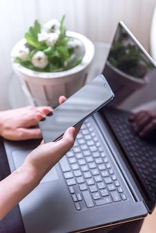 Vertikale aufnahme einer weiblichen hand, die ein smartphone und einen laptop hält