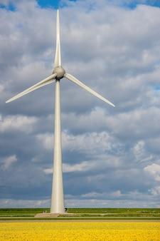 Vertikale aufnahme einer windmühle auf einer wiese mit einem bewölkten himmel im hintergrund