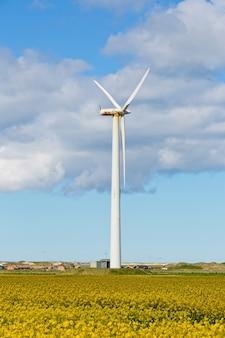 Vertikale aufnahme einer windmühle in einem feld bei bewölktem himmel