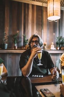 Vertikale aufnahme eines älteren mannes mit langen haaren, der in einem restaurant einen smoothie trinkt?
