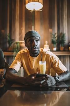 Vertikale aufnahme eines afroamerikanischen mannes, der in einem café einen smoothie trinkt?
