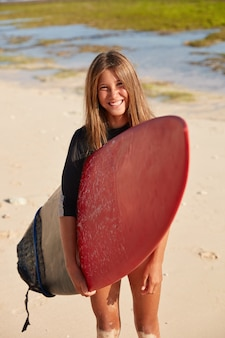 Vertikale aufnahme eines angenehm aussehenden aktiven surfers, der zum surfen bereit ist, ein rotes surfbrett trägt und freizeit am tropischen strand verbringt