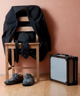Vertikale aufnahme eines anzugs auf dem stuhl neben schuhen und einer aktentasche