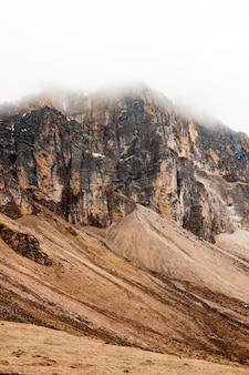 Vertikale aufnahme eines berges unter den wolken im himalaya, bhutan