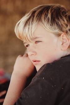 Vertikale aufnahme eines blonden australischen kaukasischen jungen, der in die ferne schaut
