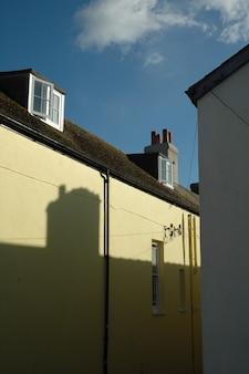 Vertikale aufnahme eines braunen und hellgelben gebäudes unter einem blauen himmel