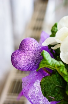 Vertikale aufnahme eines dekorativen lila herzens mit glitzer