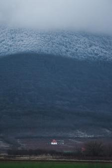Vertikale aufnahme eines einzelnen hauses im tal unter dem berg