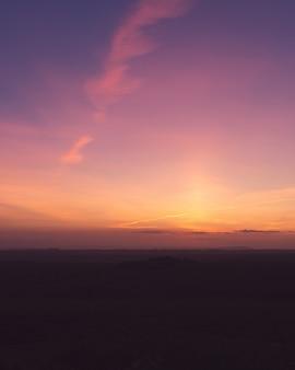 Vertikale aufnahme eines feldes unter dem atemberaubenden lila himmel