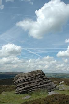 Vertikale aufnahme eines felsens auf einem gras unter einem blauen himmel mit wolken