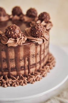 Vertikale aufnahme eines frischen schokoladenkuchens mit köstlicher schokolade auf einem teller