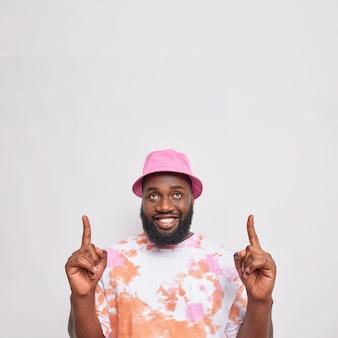 Vertikale aufnahme eines fröhlichen bärtigen afro-amerikaners, der oben auf eine leere stelle zeigt, wirbt für das produkt overhead trägt panama und ein lässiges t-shirt isoliert über weißer wand