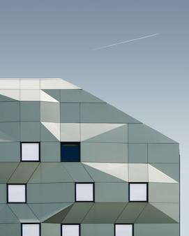 Vertikale aufnahme eines geometrischen gebäudes unter dem blauen himmel