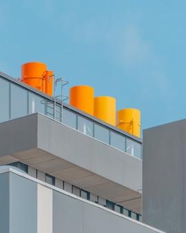 Vertikale aufnahme eines glasgebäudes mit orangefarbenen kaminen unter dem blauen himmel