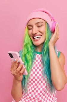 Vertikale aufnahme eines glücklichen, unbeschwerten teenagers mit langen bunten haaren wählt lieblingslied aus der playlist hält handy trägt drahtlose kopfhörer trägt hut und kleid isoliert auf rosa