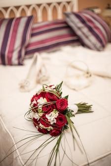 Vertikale aufnahme eines hochzeitsstraußes mit roten rosen auf dem bett