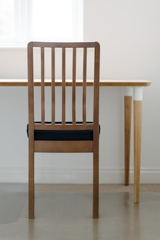 Vertikale aufnahme eines holzstuhls und eines tisches in einem weißen friedlichen raum