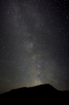 Vertikale aufnahme eines hügels mit einer atemberaubenden landschaft der milchstraße