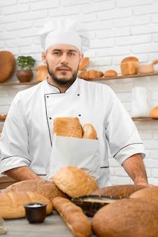Vertikale aufnahme eines jungen, gutaussehenden bäckers, der in seiner bäckerei hinter dem display voller verschiedener köstlicher brotlaibe steht, die kochende lebensmittelkochernahrung backt, die einzelhandelsgeschäftslebensmittel verkauft.