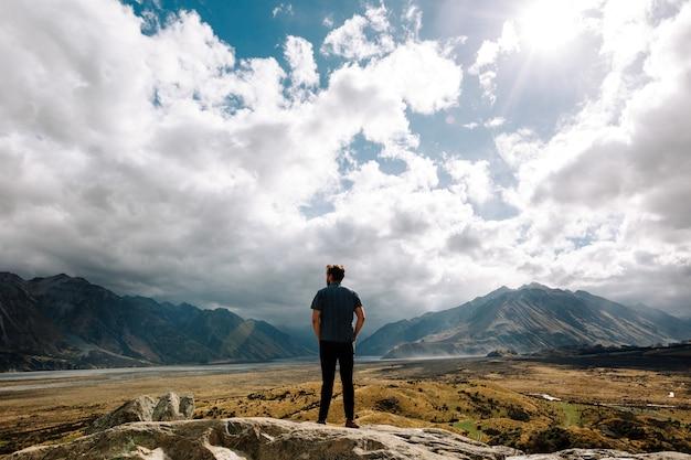 Vertikale aufnahme eines jungen mannes, der an einem sonnigen tag auf die berge starrt