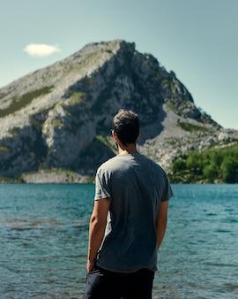 Vertikale aufnahme eines jungen mannes, der auf eine schöne seelandschaft starrt