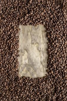 Vertikale aufnahme eines kaffeebohnenrahmens über einer holzoberfläche, die für hintergrund oder das schreiben von text groß ist
