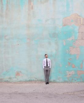 Vertikale aufnahme eines kaukasischen mannes, der ein hemd und eine krawatte trägt, während er vor einer grünen wand steht